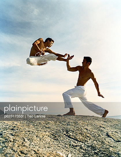 Two men performing martial arts on rocky ground