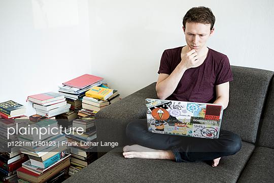 Junger Mann mit Laptop und Büchern - p1221m1150123 von Frank Lothar Lange