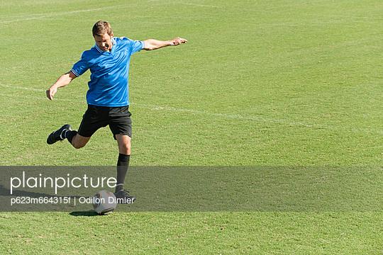 Soccer player kicking soccer ball on soccer field