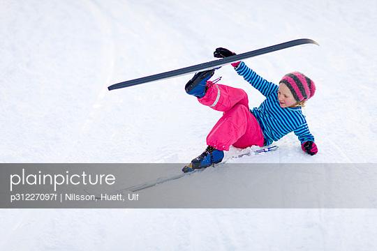 Young girl adjusting skis