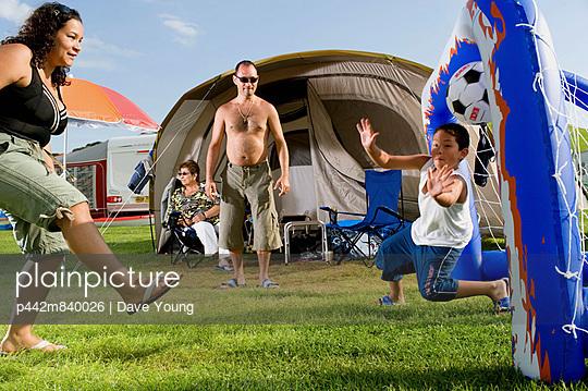 UK, England, Family playing football in Freshwater Beach Holiday park on Jurassic Coast; Dorset