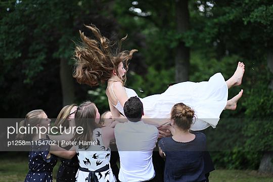Junge Leute werfen Freundin in die Luft - p1258m1154702 von Peter Hamel