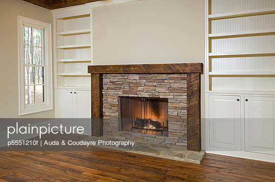 Stone fireplace with fire and bookshelves