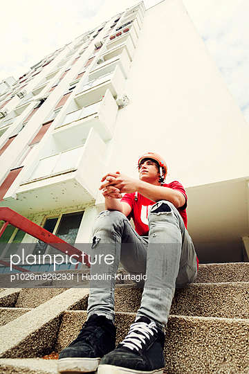 BMX biker resting on stairs with folded hands