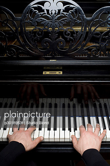 Human hands playing a piano