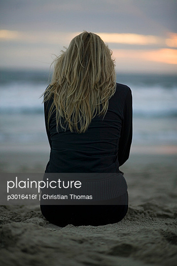 A woman sitting on a beach at sunset