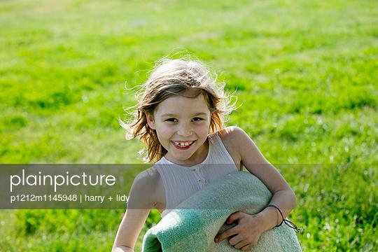 Mädchen auf dem Rasen mit gefaltener Wolldecke - p1212m1145948 von harry + lidy