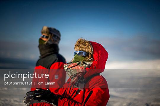 Pärchen schaut mit Sonnenfinsternis Brillen in die Sonne, Spitzbergen, Svalbard, Norwegen - p1316m1161151 von Tom Lamm