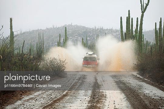 Truck Driving Through Flooded Road In Desert