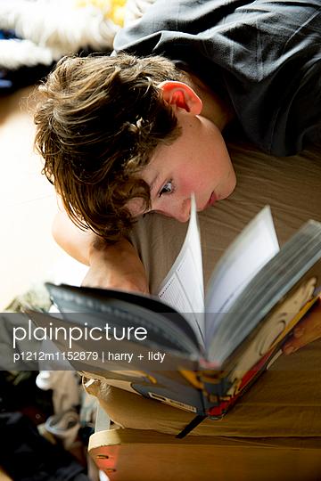 Junge liest im Bett - p1212m1152879 von harry + lidy