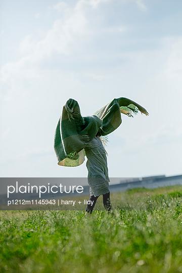 Mädchen spielt mit Wolldecke - p1212m1145943 von harry + lidy
