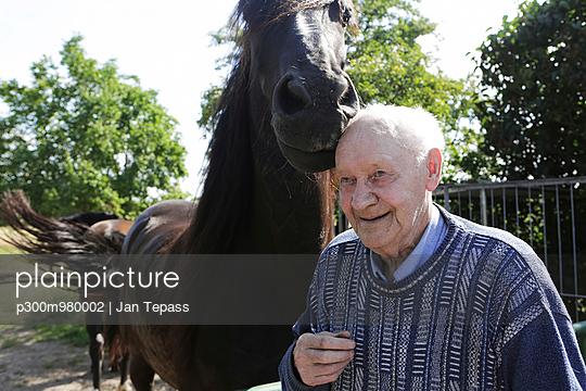 Germany, Senior man standing beside horse, smiling