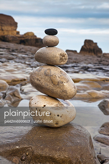 A pile of rocks balancing from largest to smallest on a boulder at the water\'s edge; south shields tyne and wear england