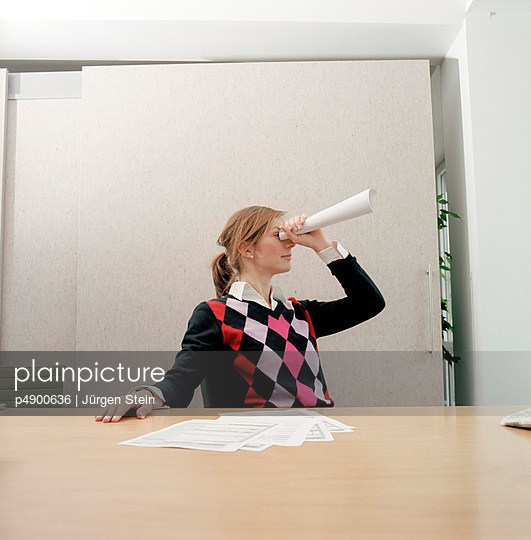 Woman in an office looking through a paper roll