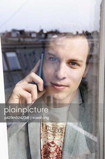 Man on mobile phone behind window