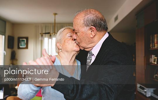 Senior couple kissing and dancing at home