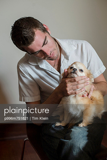A Man Pets His Long Haired Chihuahua In His Home.