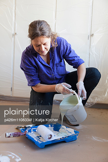 Woman pouring paint in container