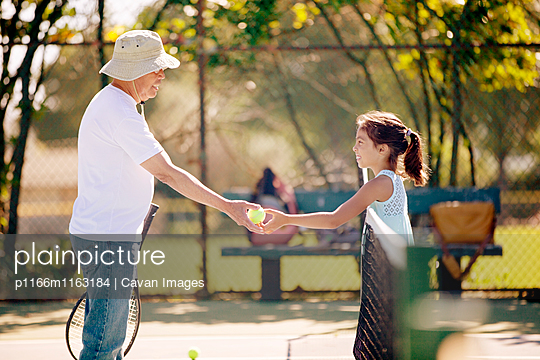 Granddaughter giving tennis ball to grandfather at court