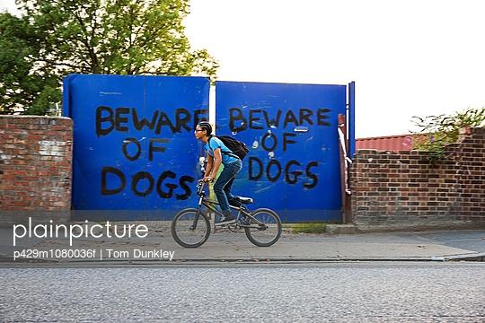 Boy riding BMX bicycle along urban sidewalk