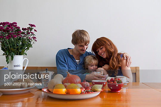 A young family sitting side by side having breakfast