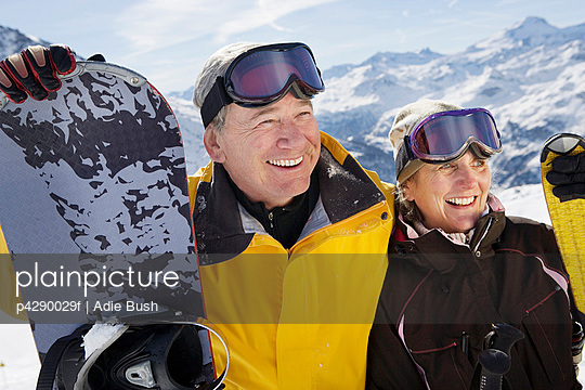 Mature couple in ski-wear holding Skis and snowboard on mountain, close-up, portrait