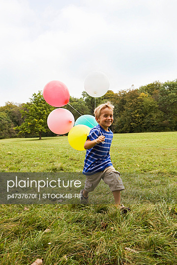 Happy boy running in meadow with balloons, Munich, Bavaria, Germany