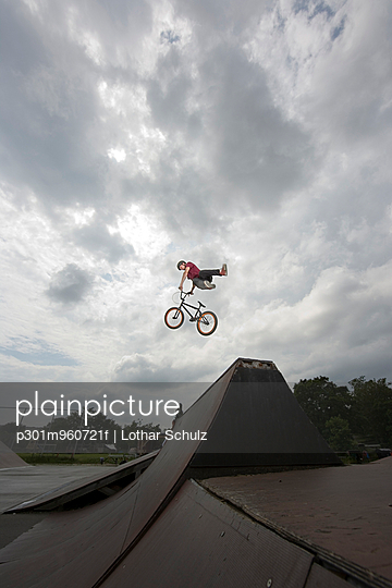 A BMX rider doing a stunt in mid air