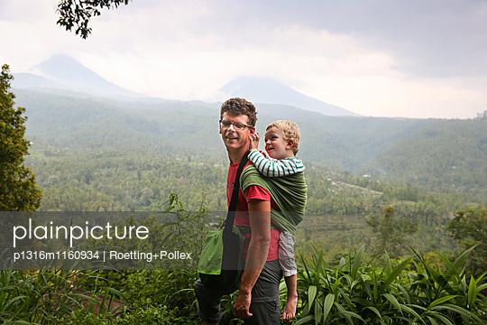 Vater wandert mit seinem Sohn, Tragetuch, auf dem Rücken, Junge 3 Jahre alt, Rucksack, Regen, Bergkulisse, Dschungel, Regenwald, tropische Vegetation, Elternzeit in Asien, Europäer, Deutsche, Westler, Familie, MR, Munduk, Bali, Indonesien - p1316m1160934 von Roetting+Pollex