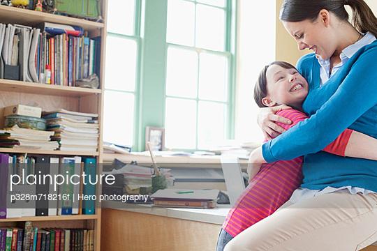 Elementary teacher hugging student.
