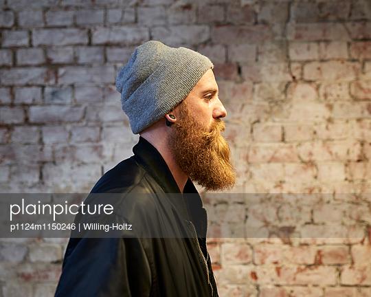 Mann mit Bart und Mütze vor einer Steinmauer im Profil - p1124m1150246 von Willing-Holtz