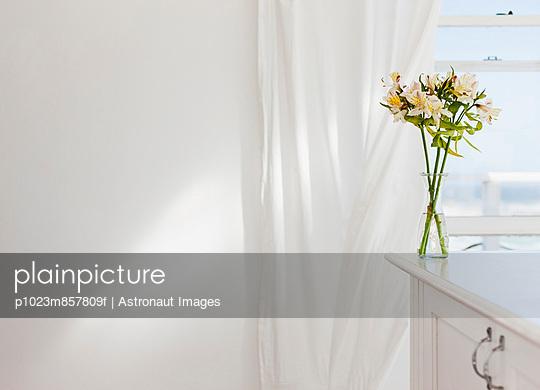Vase of flowers on desk in white room