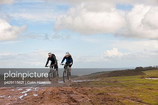 Couple riding mountain bikes through mud