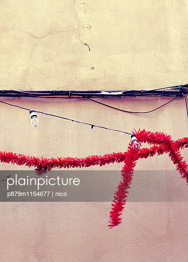 Rote Girlande an einer Hauswand - p879m1154677 von nico