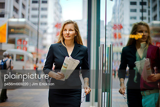 Businesswoman walking through the street carrying her newspaper.