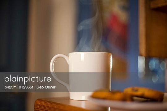 Mug of coffee and cookies on table