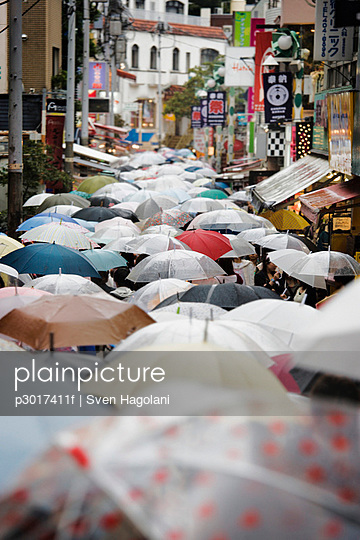 A street in Japan crowded with people carrying umbrellas