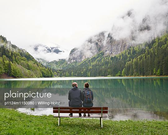 Paar sitzt auf Bank am Lac de Montriond - p1124m1150080 von Willing-Holtz