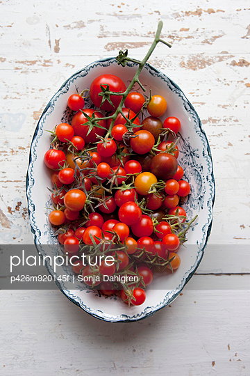 Directly above shot of cherry tomatoes in container on wood