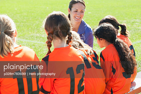 Soccer girls team listening to coach.