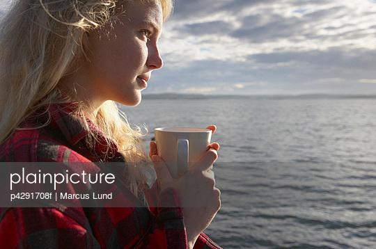 Young Woman By sea with mug of tea.