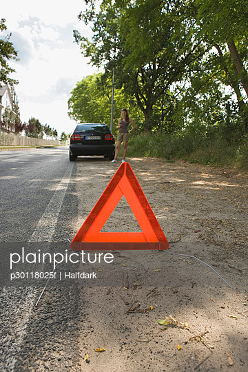A warning triangle behind a car on the side of a road