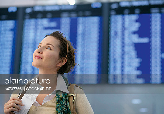 Woman holding a ticket and looking up, Munich airport, Bavaria, Germany