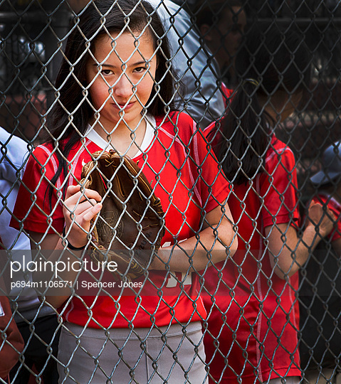 Teen Girl Playing Softball, Portrait behind Fence
