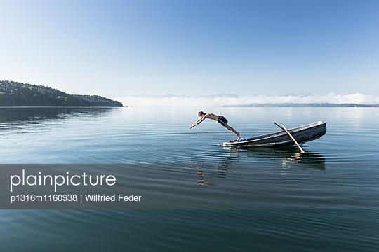 Mann schwimmt im Starnberger See, Alpen mit Zugspitze im Morgennebel, Berg, Oberbayern, Bayern, Deutschland - p1316m1160938 von Wilfried Feder