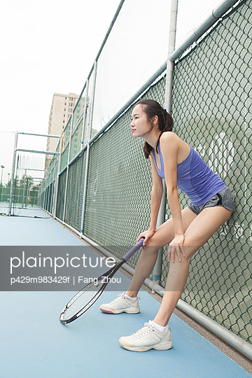Young female tennis player leaning against fence on tennis court