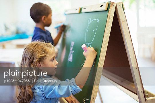 Students drawing on chalkboard in classroom