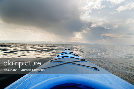 The front of a blue kayak floats across the water of Flathead Lake, Montana, as an evening storm builds in the distance