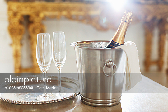 Champagne in silver bucket next to champagne flutes
