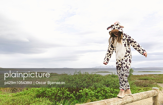 Girl wearing animal onesie balancing on wooden fence, Thingvellir, Iceland